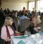 Mystery writers Lisa Kleinholz and Carol Shmurak confer at lunch.
