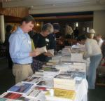Gary Urey of the Write Angles planning committee and others browse at the Odyssey's book table.